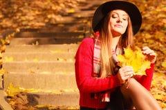 放松在秋天秋天公园的妇女 免版税库存图片