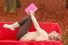 放松在秋天秋天公园阅读书的妇女 免版税库存图片
