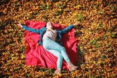 放松在秋季公园的女孩说谎在红色毯子 免版税库存图片