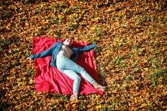放松在秋季公园的女孩说谎在红色毯子 库存照片