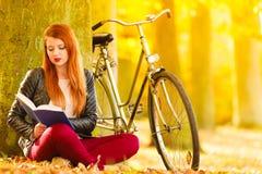 放松在秋季公园阅读书的妇女女孩 免版税库存照片