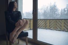 放松在窗口前面的妇女,当下雪时 免版税库存图片
