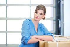 放松在箱子旁边的女实业家的画象在仓库里 免版税库存图片