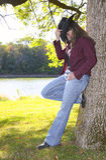 放松在结构树下的女牛仔 库存图片