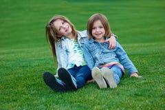 放松在绿草的愉快的孩子在夏天停放 免版税库存图片