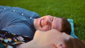 放松在绿草的愉快的微笑的夫妇 男性在焦点 股票视频