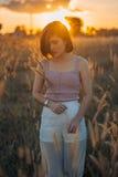 放松在美好的日落的一个少妇的剪影 库存照片