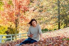 放松在美好的秋天天的快乐的妇女, 图库摄影