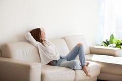 放松在舒适的沙发的愉快的妇女享受周末在hom 免版税库存图片