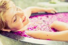 放松在花浴的妇女 免版税库存照片