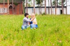 放松在草坪的愉快的年轻夫妇在一个夏天停放 概念亲吻妇女的爱人 假期 图库摄影
