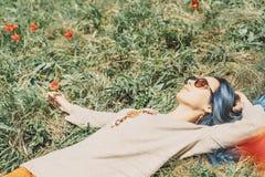 放松在草甸的美丽的女孩 免版税库存图片