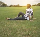 放松在草的亚裔人享用在一天在一个公园有天空背景,泰国 免版税图库摄影