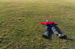 放松在草的妇女。背景 库存图片