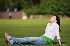 放松在草的美丽的妇女 免版税图库摄影