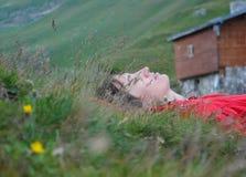 放松在草的美丽的妇女 库存图片