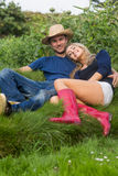 放松在草的逗人喜爱的夫妇 图库摄影