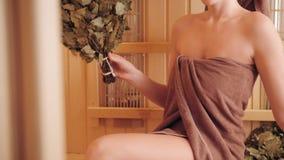 放松在蒸汽浴的年轻女人穿戴在毛巾 新的芬兰蒸汽浴内部,医疗的红外盘区 影视素材