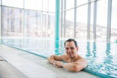 放松在豪华屋顶游泳池和微笑对照相机的年轻人对五个星旅馆温泉 免版税库存照片
