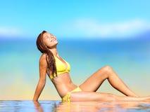 放松在豪华温泉的太阳下的晒日光浴的妇女 免版税库存图片
