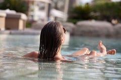 放松在豪华游泳池边的美丽的妇女 免版税图库摄影