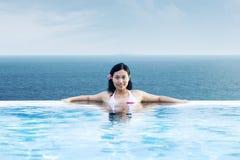 放松在豪华水池的亚裔妇女由海滩 免版税图库摄影
