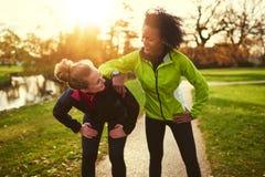 放松在跑步以后的两个女运动员 库存图片