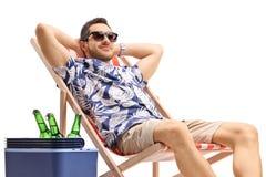 放松在轻便折叠躺椅的年轻男性游人在有瓶的一个冷却的箱子旁边啤酒 库存照片