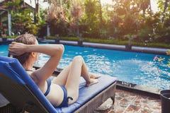 放松在轻便折叠躺椅的比基尼泳装的美丽的妇女在游泳池附近在旅馆里 库存图片