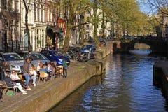 放松在边路咖啡馆的人们由一条河运河在Amsterd 库存图片