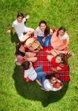 放松在野餐毯子的七个愉快的朋友 免版税库存图片