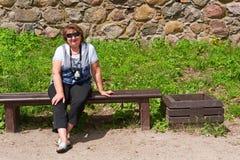 放松在长凳的中年妇女 库存图片