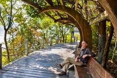 放松在长凳的人在中国荫径下 免版税图库摄影