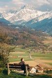 放松在长凳的人,敬佩瑞士阿尔卑斯 库存照片