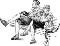 放松在长凳的夫妇 免版税库存照片