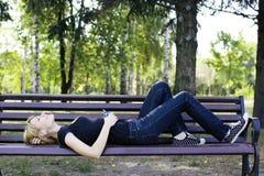 放松在长凳的妇女,听到音乐。 免版税库存照片