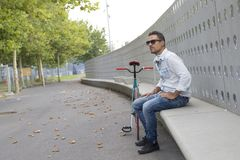 放松在长凳的年轻人骑自行车的人,当听的音乐时 免版税库存图片