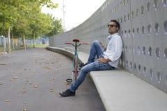 放松在长凳的年轻人骑自行车的人,当听的音乐时 库存图片