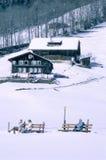 放松在长凳的游人在雪中间 免版税库存照片