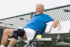放松在长凳的资深网球员 免版税库存图片
