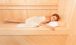 放松在长凳的逗人喜爱的小女孩在蒸汽浴 免版税图库摄影