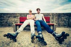 放松在长凳的青年人朋友 免版税库存照片