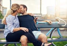 放松在长凳的年轻夫妇享受亲吻 免版税库存图片