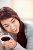 放松在长沙发的亚裔妇女用咖啡 免版税图库摄影