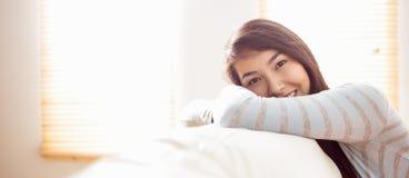 放松在长沙发的亚裔妇女 免版税图库摄影