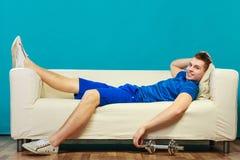 年轻放松在长沙发的人适合的身体在训练以后 免版税库存图片