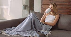 放松在长沙发的年轻白肤金发的妇女 免版税图库摄影