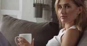 放松在长沙发的年轻白肤金发的妇女 库存照片