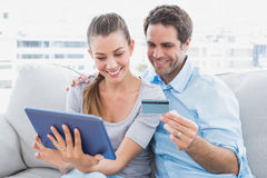 放松在长沙发的愉快的夫妇在网上购物与片剂个人计算机 库存照片