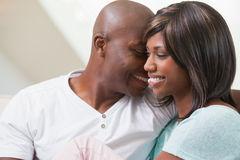放松在长沙发的愉快的夫妇 免版税库存图片
